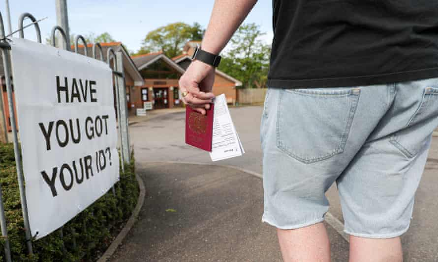 A voter brings his passport to the polling station in the 2018 local election in Woking