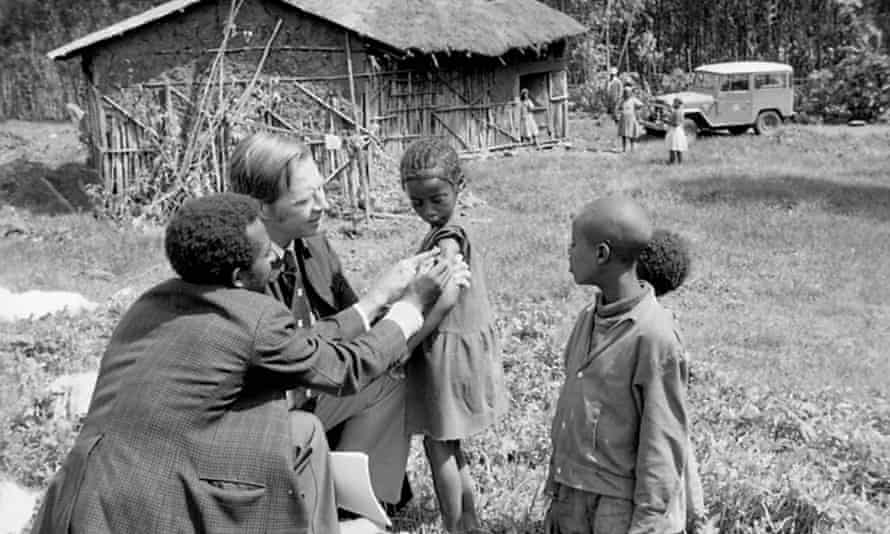 Donald Henderson, second from left, examines vaccination scars on children in Ethiopia.