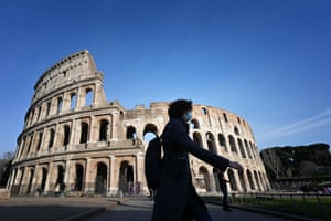 A tourist wearing a respiratory mask as part of precautionary measures against coronavirus walks past the closed Colosseum in Rome