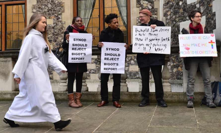 A delegate walks past activists from the Lesbian and Gay Christian Movement outside the General Synod at Church House in London.