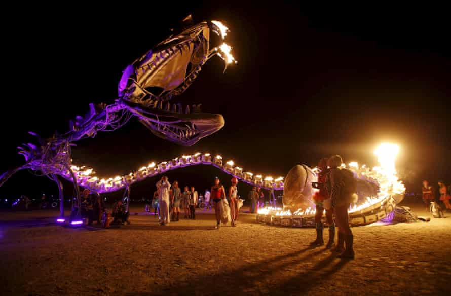 People gather at the art installation Serpent Mother.