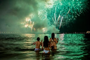 People watch fireworks from the water on Copacabana beach in Rio de Janeiro, Brazil