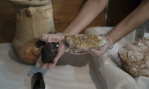 A researcher holds an original amethyst, left, and an amethyst which was transformed into a yellow citrine stone due to the high temperatures caused by the fire that swept through the National Museum in September.