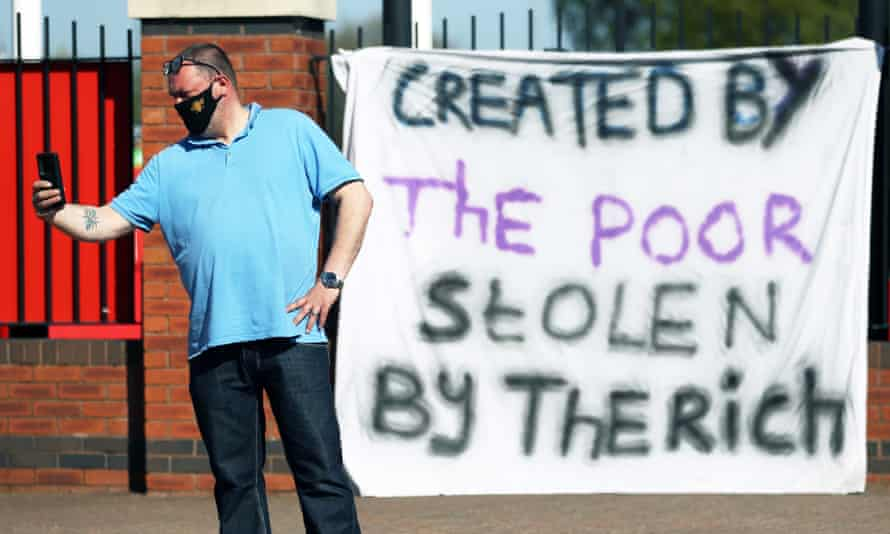 A member of the public poses for a photo in front of a sign opposing the European Super League hung outside Old Trafford in Manchester.