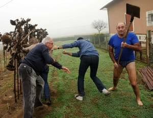 President of the Bird Protection league (LPO), Allain Bougrain-Dubourg (L) is evacuated by an inhabitant after clashing with the owner (R) of a plot where bird traps were found