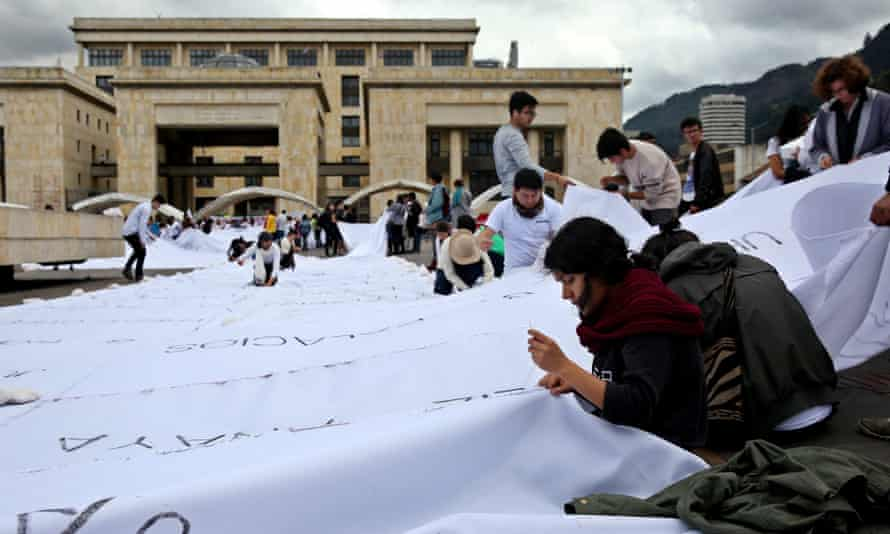 A group of people participate in an artistic intervention lead by the Colombian artist Doris Salcedo in Bogota Tuesday.
