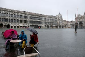 Venice, Italy Tourists sit in a flooded St Mark's square during a period of seasonal high water