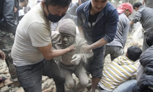 People free a man from the rubble of a destroyed building in Kathmandu after the earthquake hit