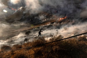 Nicosia, Cyprus: A firefighter douses flames in an effort to contain the island's worst fire in decades.