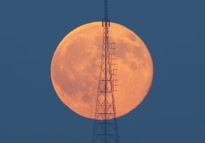 The moon is seen behind a telecommunications tower in Istanbul, Turkey.