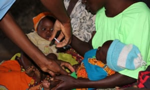 Brian Chimpuku administers the malaria vaccine to a five-month old child in Mkaka, Malawi