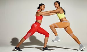 Shannon and Cheriece Hylton in athletics kit, a profile view of them pushing into each other's shoulders, their long legs in a stride