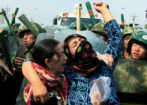 A woman yells as Chinese paramilitary police confront a crowd of angry locals in the city of Urumqi, the capital of China's far northwester region of Xinjiang on 7 July, 2009.