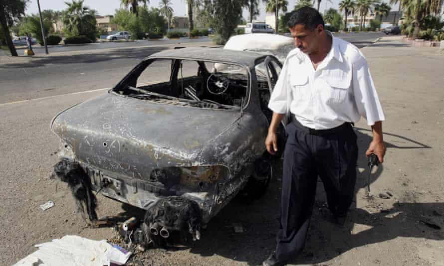 An Iraqi traffic policeman inspects a car destroyed by a Blackwater security detail in Baghdad, Iraq, on 25 September 2007.
