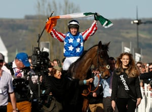 Noel Fehily holds aloft the flag of Ireland as he celebrates his victory as Special Tiara enters the winner's enclosure.