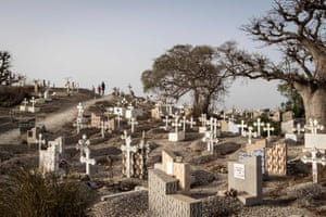People walk through a mixed Catholic and Muslim cemetery