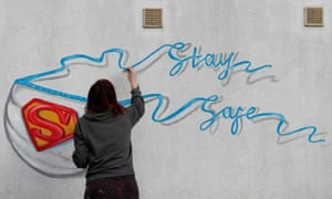 The artist Rachel List paints a mural featuring the Superman symbol and a facemask