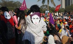 People wear masks depicting Qandeel Baloch, as they take part in a women's march in Karachi, 8 March 2018