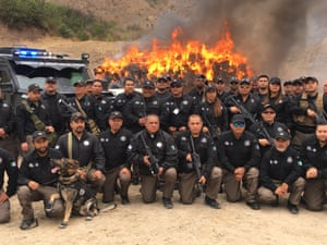Law enforcement agents pose in front of a bonfire of drugs, Tijuana.