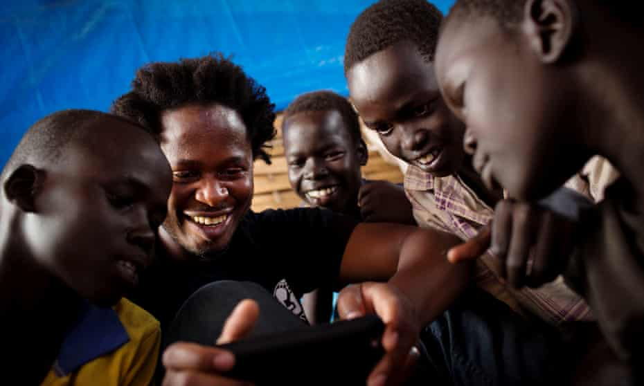 Ishmael Beah talks to a group of children at a school in Pibor, South Sudan