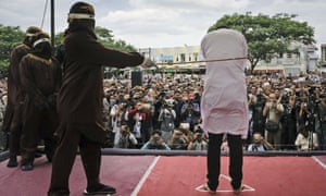 A sharia law official canes a man convicted of gay sex during a public caning in Banda Aceh, in May last year.