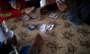Teenage boys play a game of cards at a migrant shelter for unaccompanied minors in Tijuana, Mexico, 5 December 2018.
