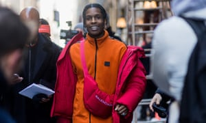 A$AP Rocky wearing a red down feather jacket, Balenciaga bag, orange zip jacket outside Calvin Klein on February 10, 2017 in New York City