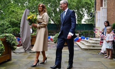 Melania Trump, complete with vertiginous heels, with Philip May at a Downing Street garden party.