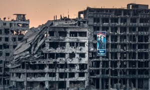 June 2014: .An election campaign poster for President Bashar al-Assad hangs on a ruined shopping mall in Homs.