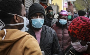 People wait for a distribution of masks and food from the Rev. Al Sharpton in the Harlem neighborhood of New York.