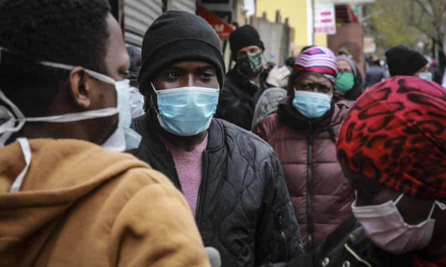 People wait for a distribution of masks and food in Harlem, New York. Many black Americans are already feeling the economic pinch of the coronavirus.