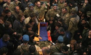 People attend a memorial service for an Armenian serviceman killed in clashes in Nagorno-Karabakh.