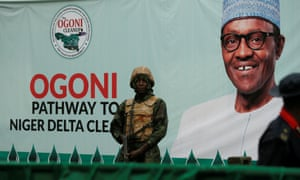 A soldier stands guard in front of a banner with a picture of Nigeria's President Muhammadu Buhari in Gokana, Nigeria, during the launch of an exercise to clean up pollution in Ogoniland, in June 2016.
