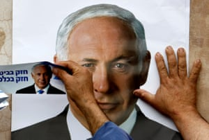 Yarka, Israel. A Likud party supporter puts up a poster of the Israeli prime minister, Benjamin Netanyahu