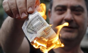 An anti-austerity protester burns a €5 note during a demonstration in Athens.