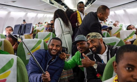 Passengers pose for a selfie onboard a flight from Addis Ababa to Asmara