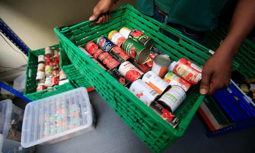 Box of canned food being held by volunteer at foodbank