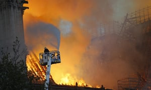A fire fighter uses a hose on the burning Notre Dame cathedral in Paris on Monday.