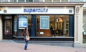 Woman looks at Supercuts store window