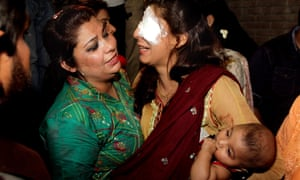 A woman injured in the bomb blast is comforted by a relative at a hospital in Lahore.