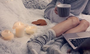 A woman relaxes at home with candles.