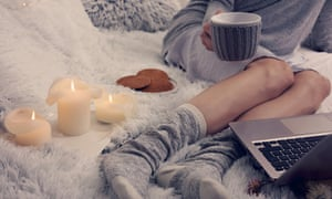 Cozy evening , warm woolen socks, soft blanket, candles. Woman relaxing at home,drinking cocoa, using laptop.
