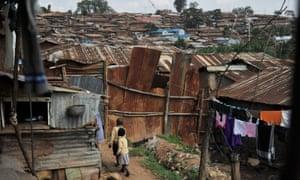 Two school children walk through a slum