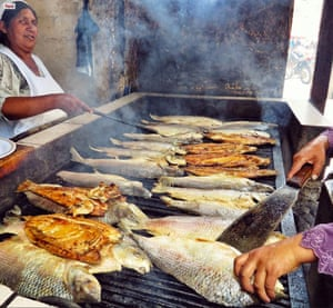 Fish being fryed on a griddle at an outdoor market in Sucre, Bolivia.