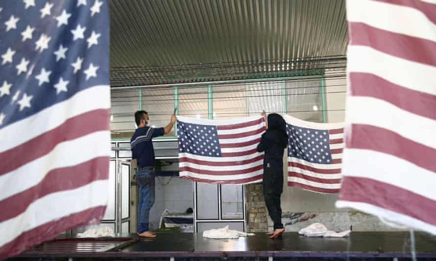 Iranian workers collect US flags after making them at a flag factory in Khomein, Iran, on 28 January.