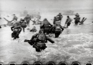 "American soldiers landing on Omaha Beach, D-Day, Normandy, France. June 6, 1944. Robert Capa International Center of Photography/Magnum Photos ""The water was cold, and the beach still more than a hundred yards away. The bullets tore holes in the water around me, and I made for the nearest steel obstacle... It was still very early and very gray for good pictures, but the gray water and the gray sky made the little men, dodging under the surrealistic designs of Hitler's anti-invasion brain trust, very effective."" – Robert Capa, Slightly Out of Focus (1947)"