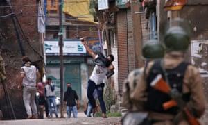 A protester throws a stone