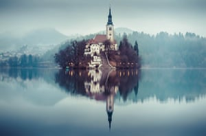 The pilgrimage Church of the Assumption of Mary, on an island in Lake Bled, Slovenia, taken by Sandi Bertoncelj and entitled Deep Silence. This is early morning shot, with the hanging mist creating a mystical feel.