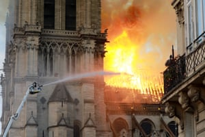 A firefighter is seen fighting the flames at Notre-Dame Cathedral