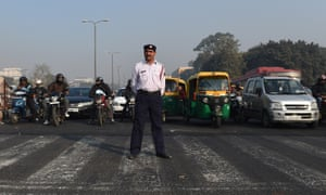 A traffic police officer at an intersection in New Delhi. Millions of Delhi drivers will have to find alternative ways to get to work from 1 January.